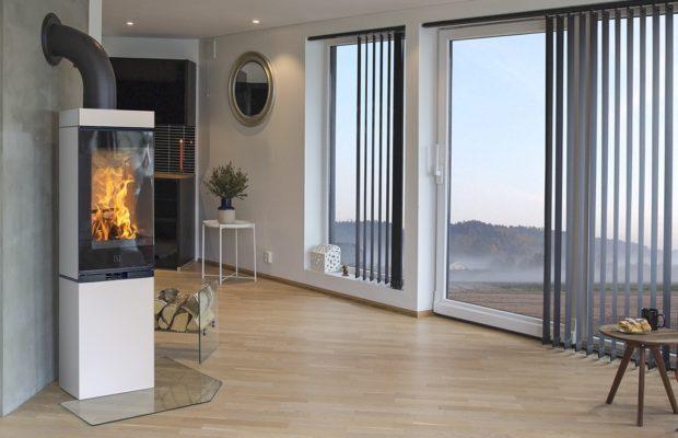 Scan 80 hvit peisovn med panorama innsyn til bålet gjennom 90 graders bøyd glass og panorama innsyn til flammene. Vist i moderne interiør